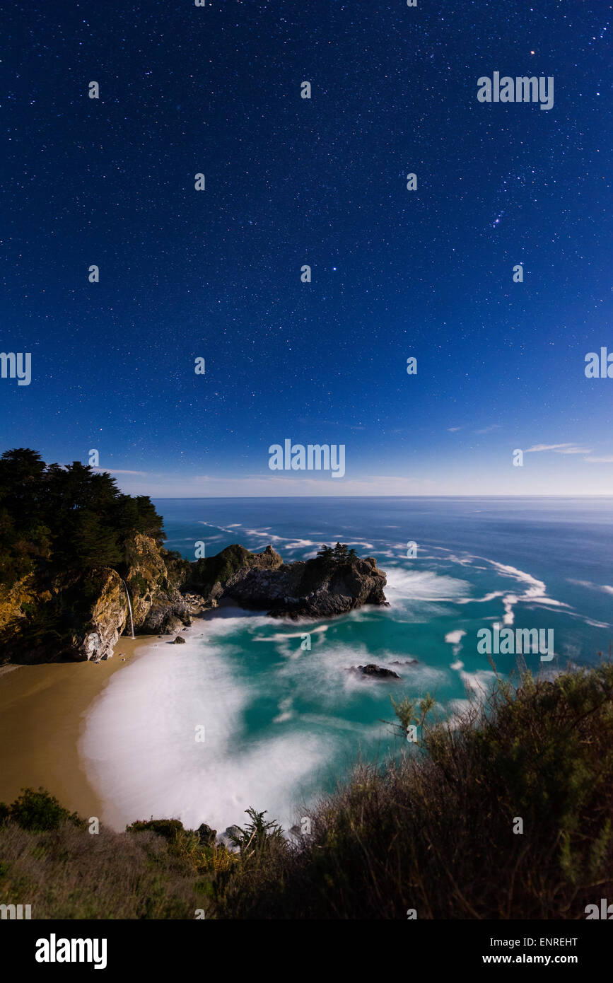 Beautiful sunset of McWay Falls into the Pacific Ocean along the Big Sur Coast of California just north of the Esalen Stock Photo