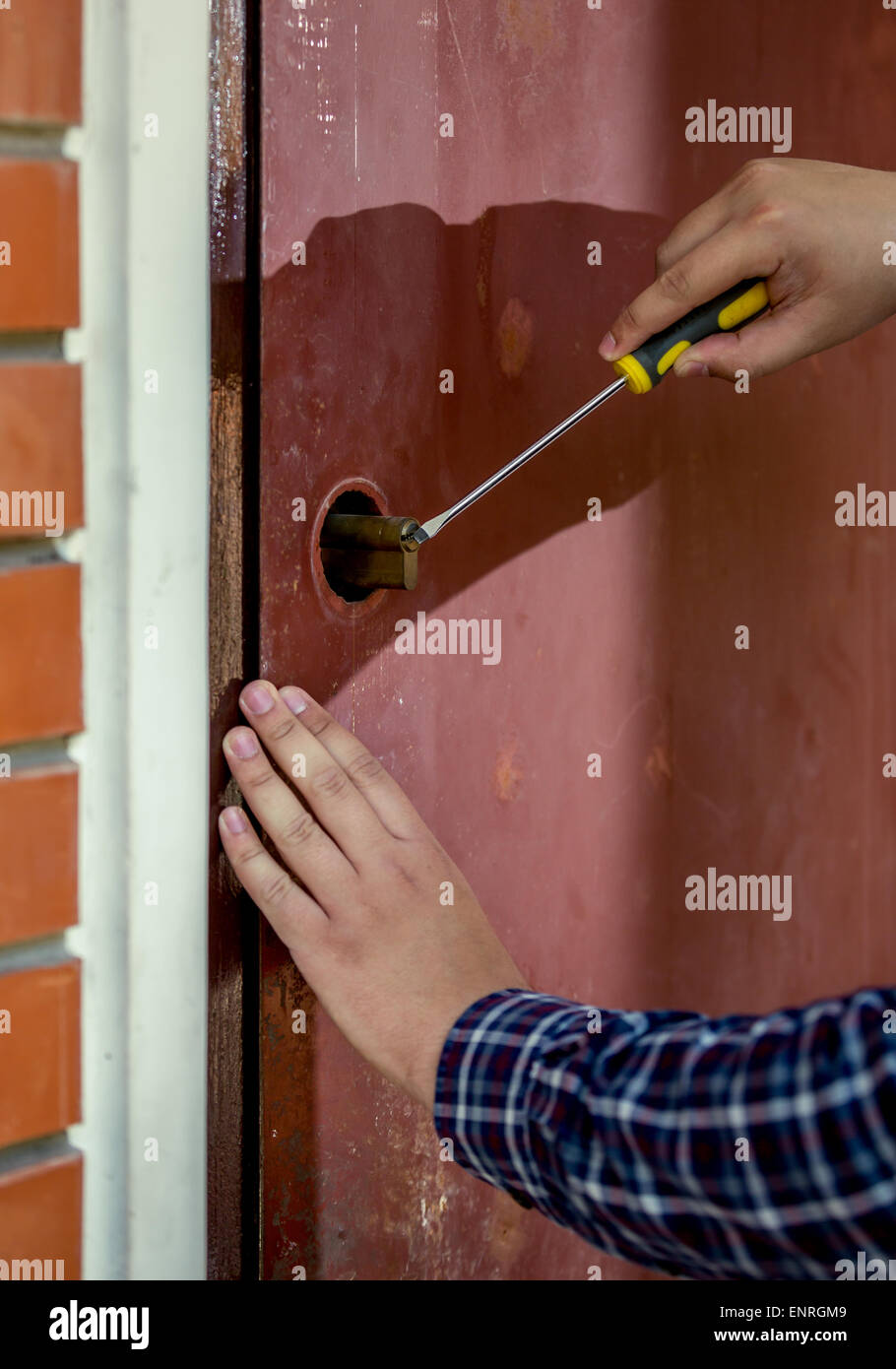 Closeup Shot Of Carpenter Trying To Open Door Lock Using Screwdriver
