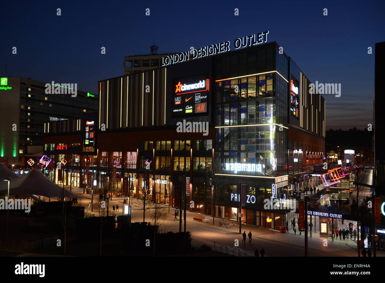 London Designer Outlet at Wembley Park Boulevard illuminated shops at night - Stock Image