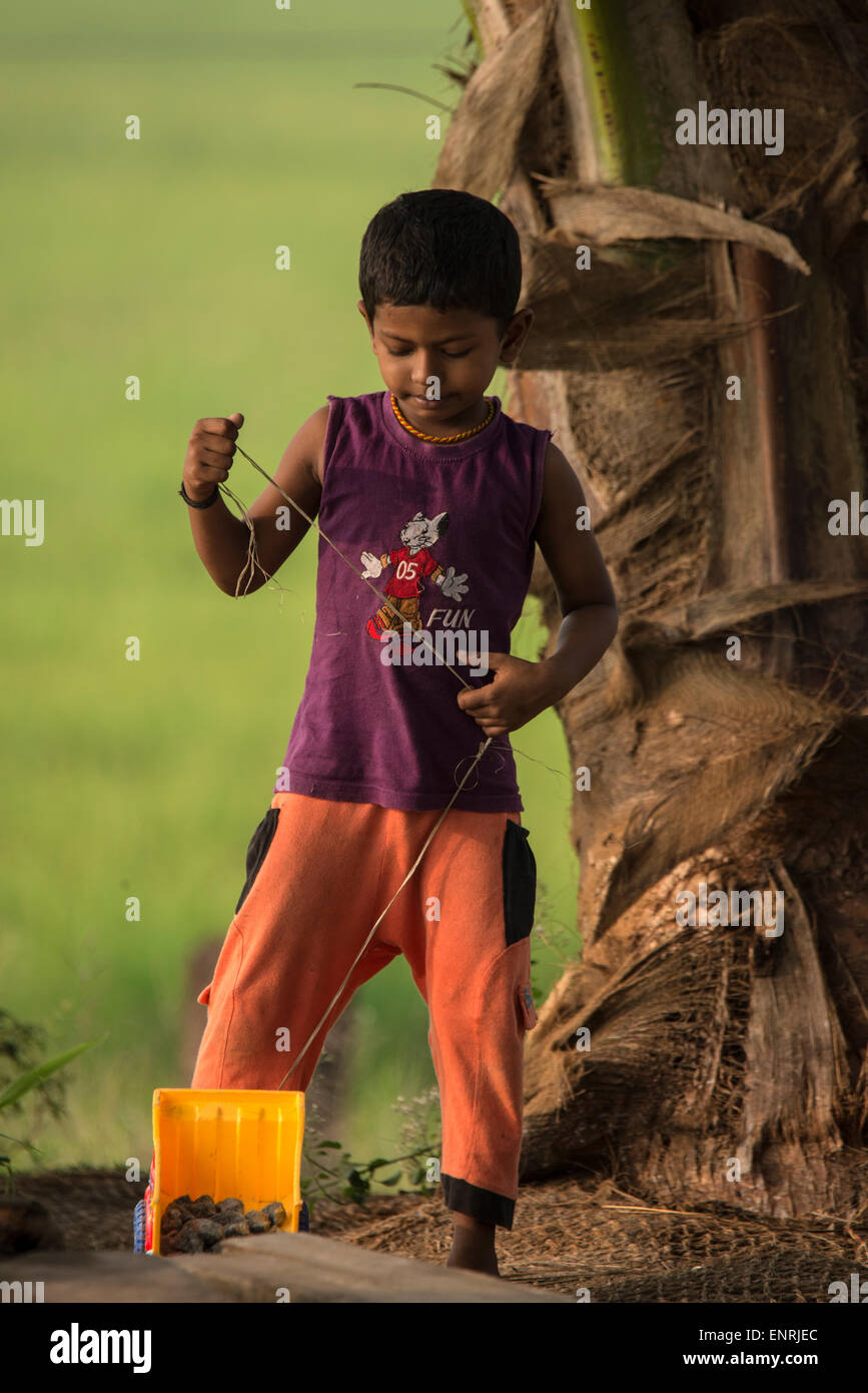 A young India boy playing with his toy truck at his home on the backwaters of Kerala in India - Stock Image