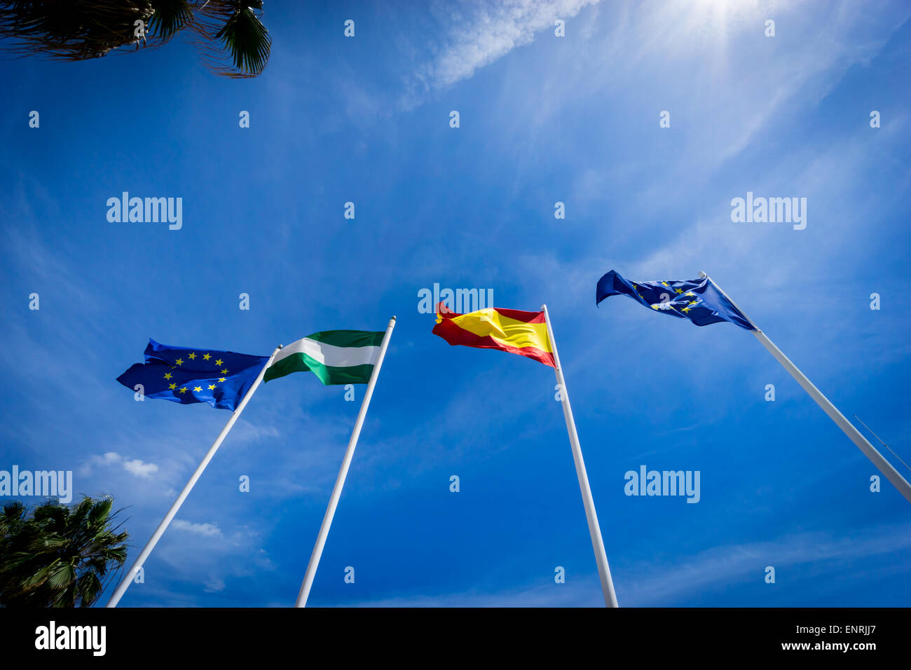 Flags of the European Union, Andalucia, and Spain seen flying in Torremolinos, Spain against a blue sky - Stock Image