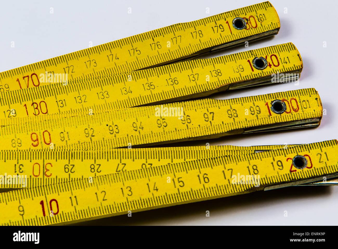 Yellow wooden folding ruler on white background - Stock Image