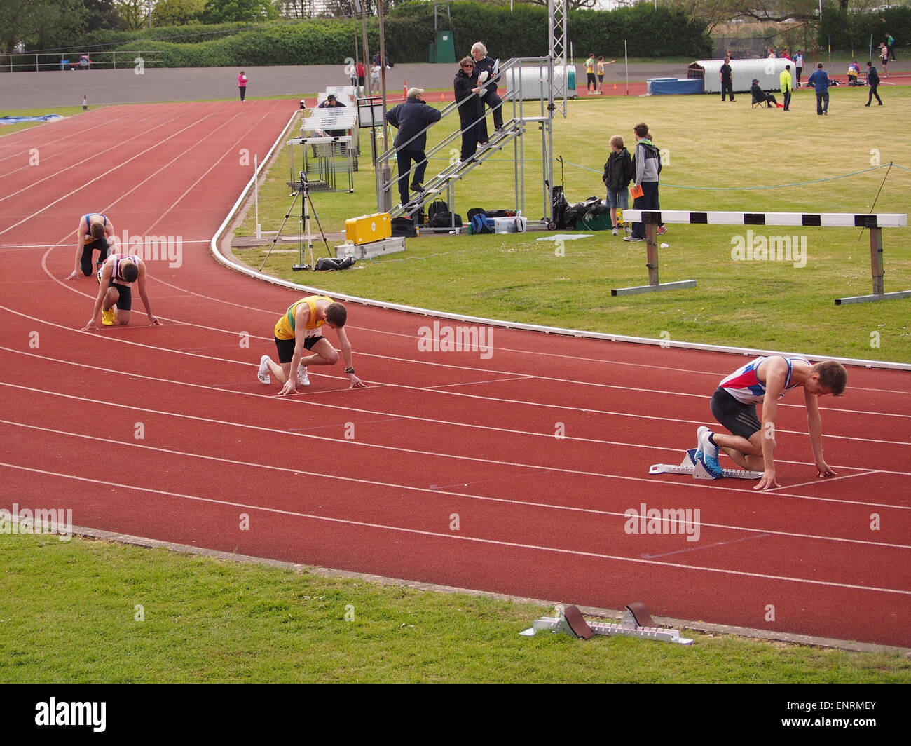 Sprinters prepare for the start of a race on a running track - Stock Image