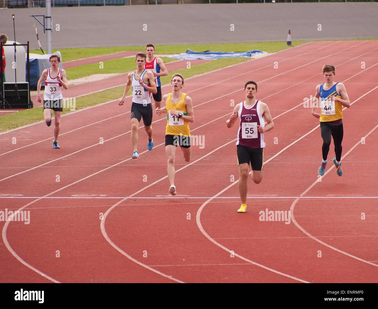 Sprinters cross the finish line of a running track - Stock Image