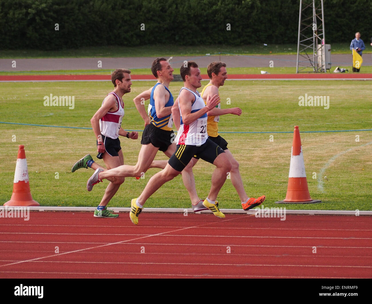 Runners sprint for the finish line during a distance race on an athletics running track - Stock Image