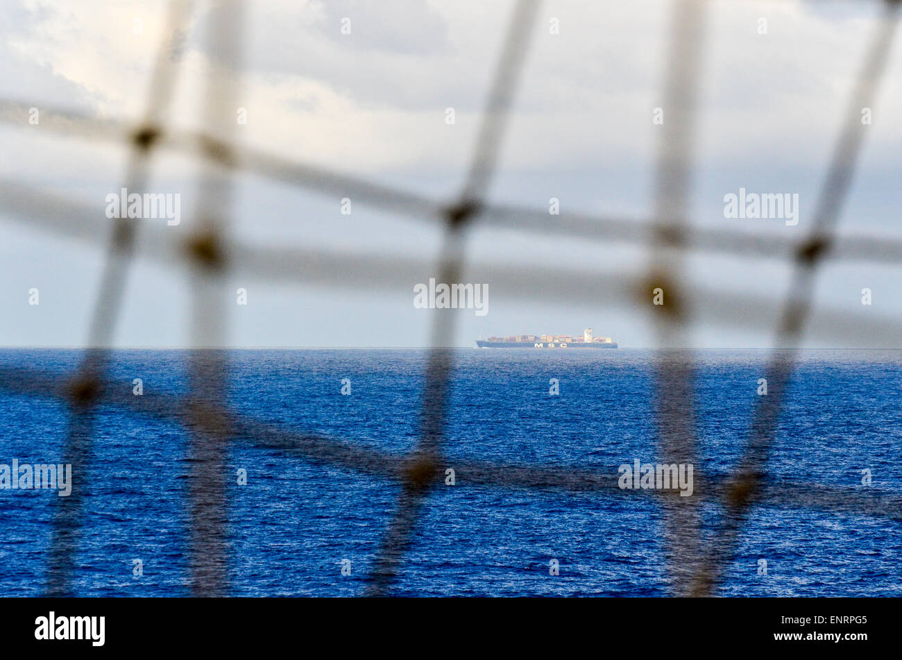 Container ship in the Atlantic ocean seen through a net - Stock Image