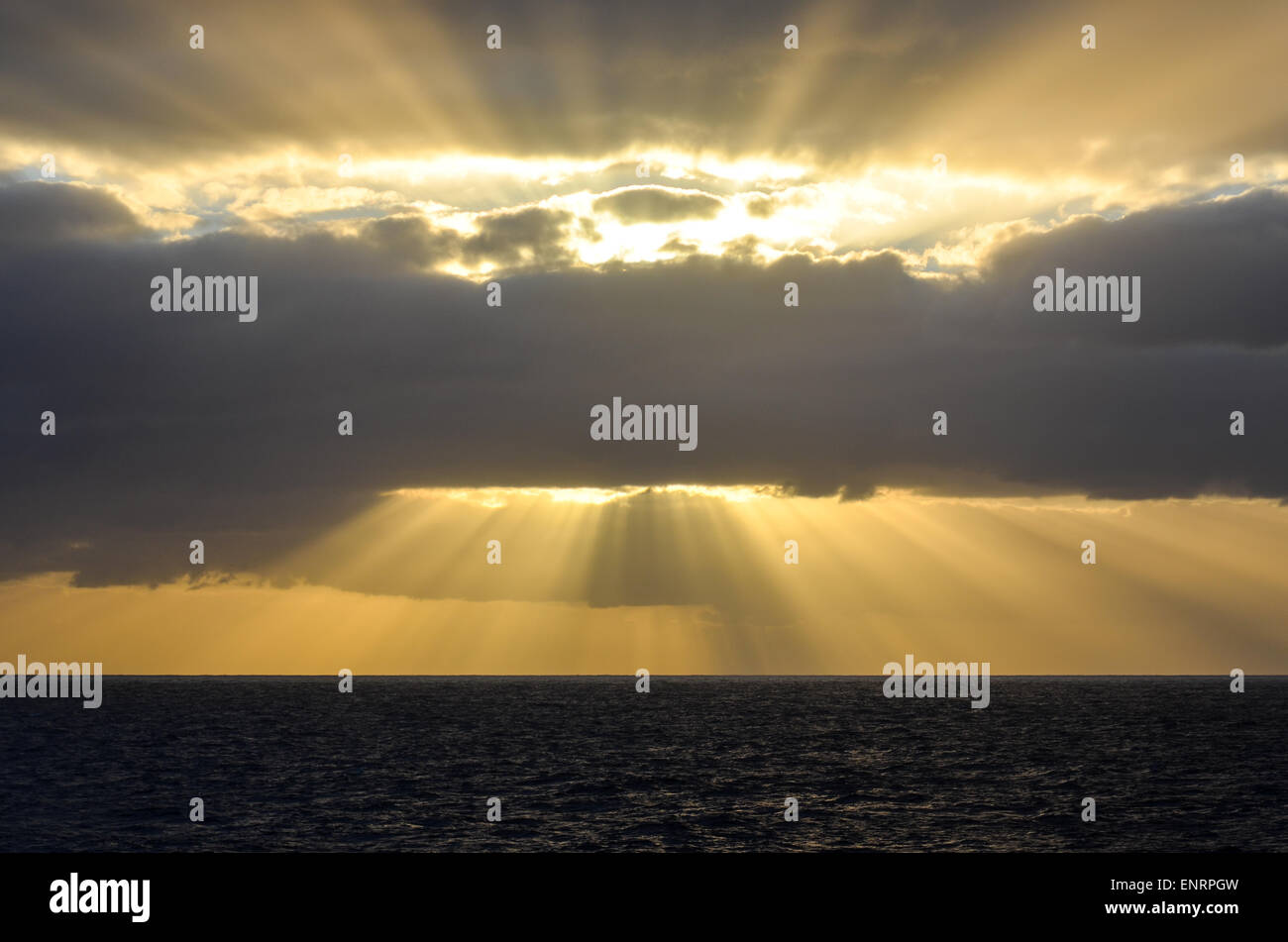 Yellow sunrays in the sky at sunrise while sailing in the Atlantic ocean - Stock Image