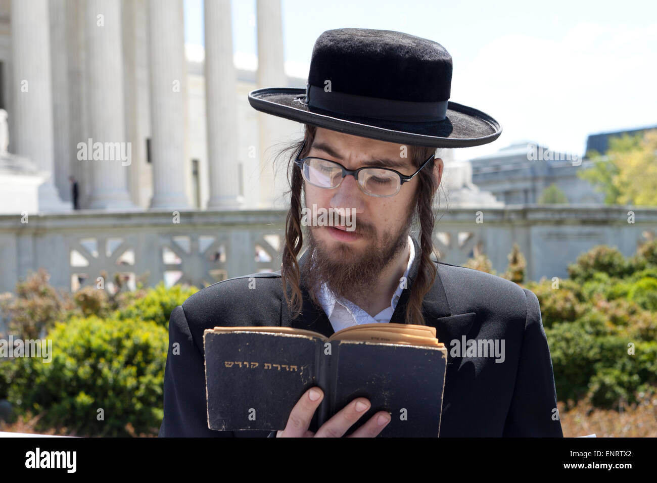 Hasidic Orthodox Jewish man reading the Torah in front of the US Supreme Court building - Washington, DC USA - Stock Image