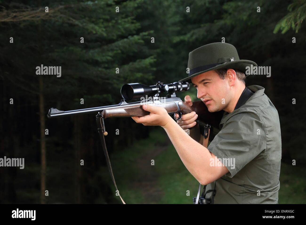 A Hunter shooting with his rifle - Stock Image