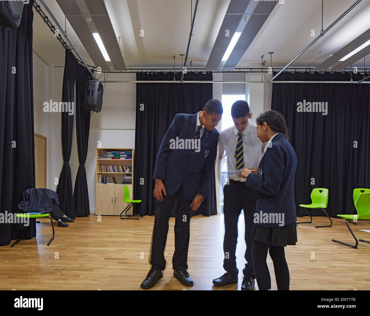 Multi-functional performance space with students. Regent High School, London, United Kingdom. Architect: Walters - Stock Image