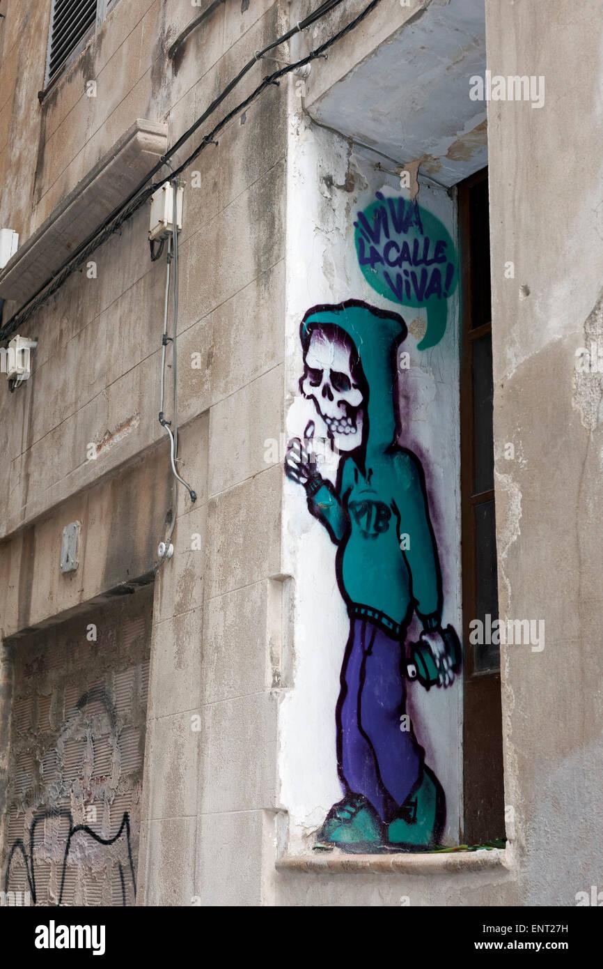 Sprayer with skull-face, hooded sweatshirt, mural, street art, Palma de Majorca, Majorca, Balearic Islands, Spain - Stock Image