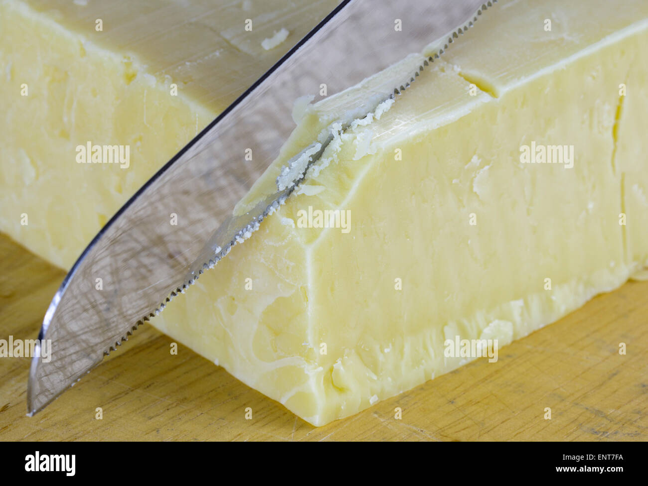 Knife cutting through yellow cheddar cheese of a chopping board. - Stock Image
