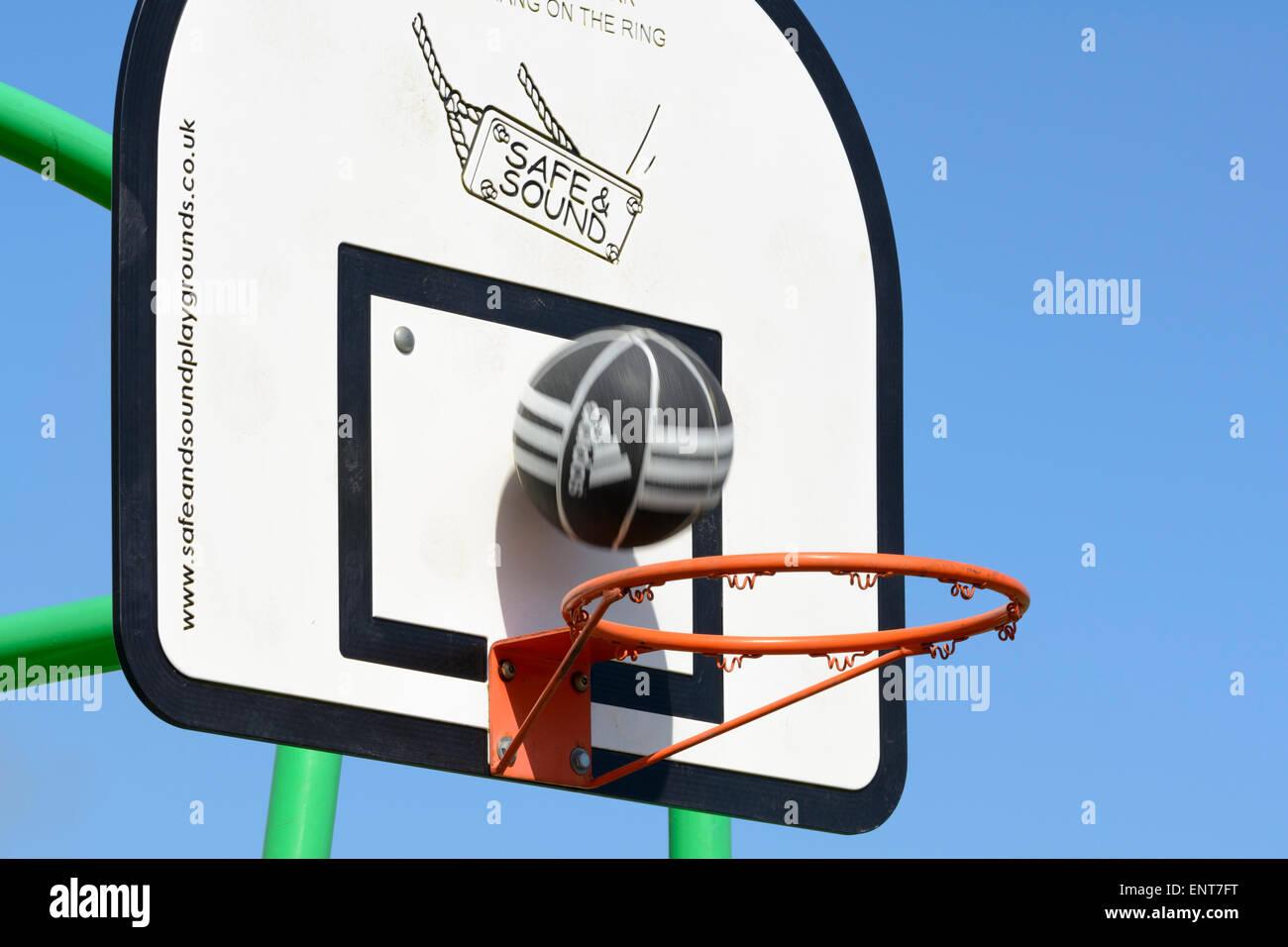Basketball going into a basketball hoop . - Stock Image