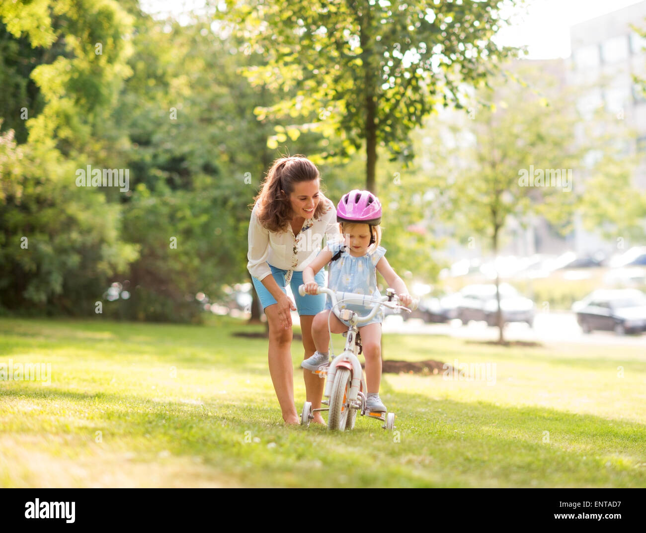 In a sunny city park, a mother gently pushes her blonde, blue-eyed daughter forward with encouragement as she learns - Stock Image