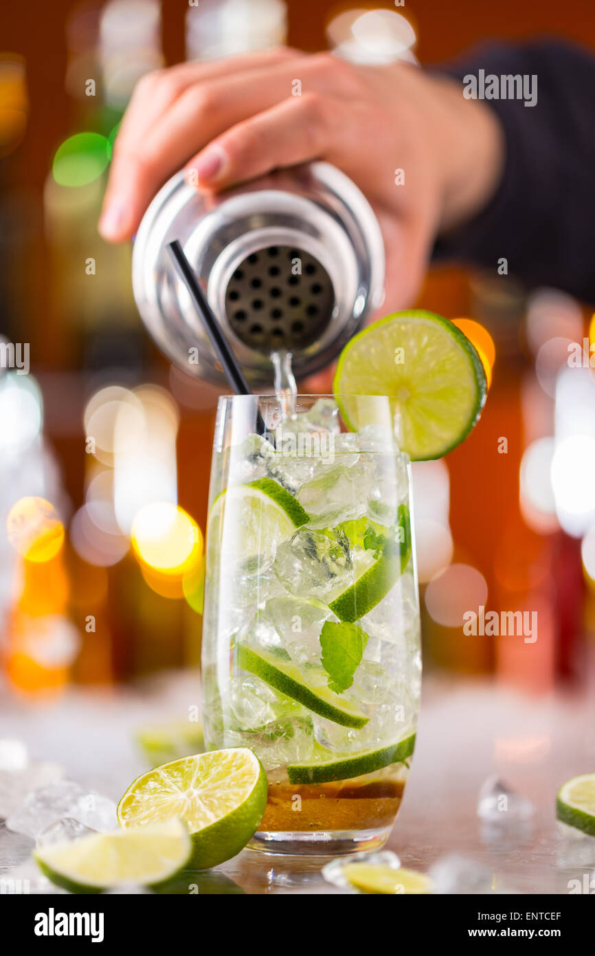 Mojito cocktail drink on bar counter with barman holding shaker - Stock Image
