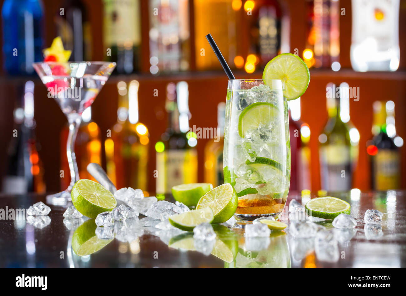 Mojito cocktail drink on bar counter with blur bottles on background - Stock Image