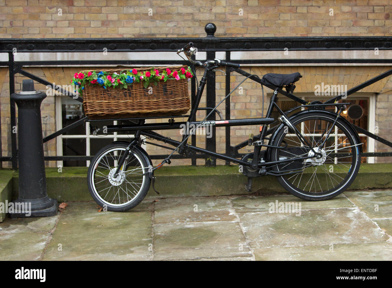 Specially-designed bicycle with a wicker basket on the front, decorated with flowers, England Stock Photo