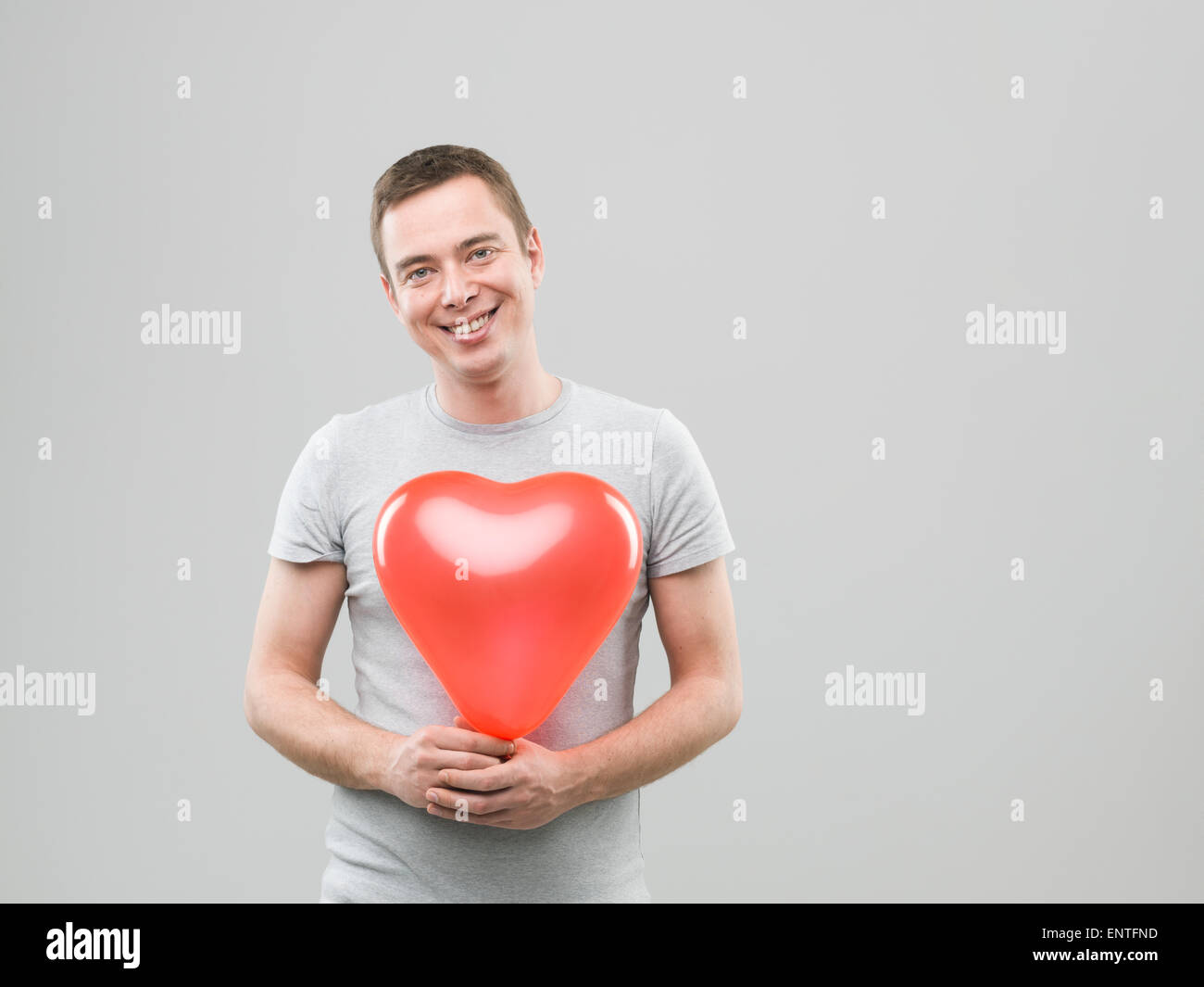 young caucasian man holding heart shaped balloon and smiling. copy space available - Stock Image