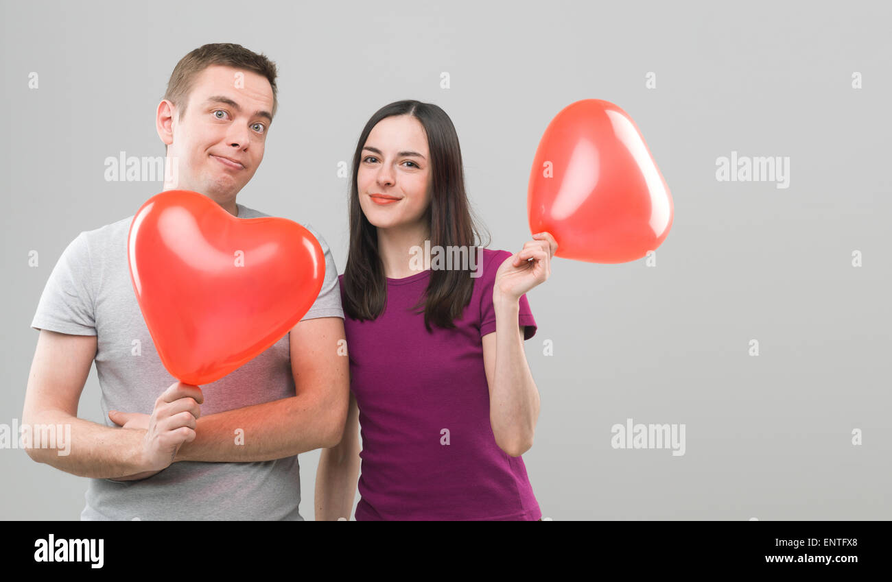 loving young couple holding heart shaped balloons and smiling. copy space available - Stock Image