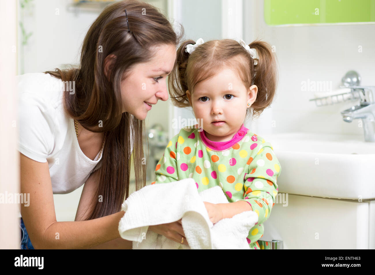 Child girl washing her hands in bathroom. Mom helps her little daughter. - Stock Image