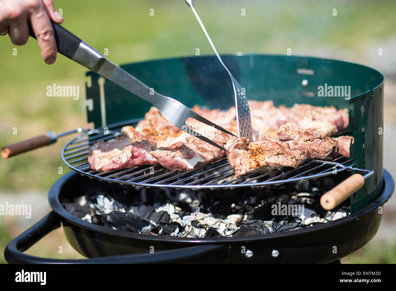 grilling pork on live coals with grill tools Stock Photo