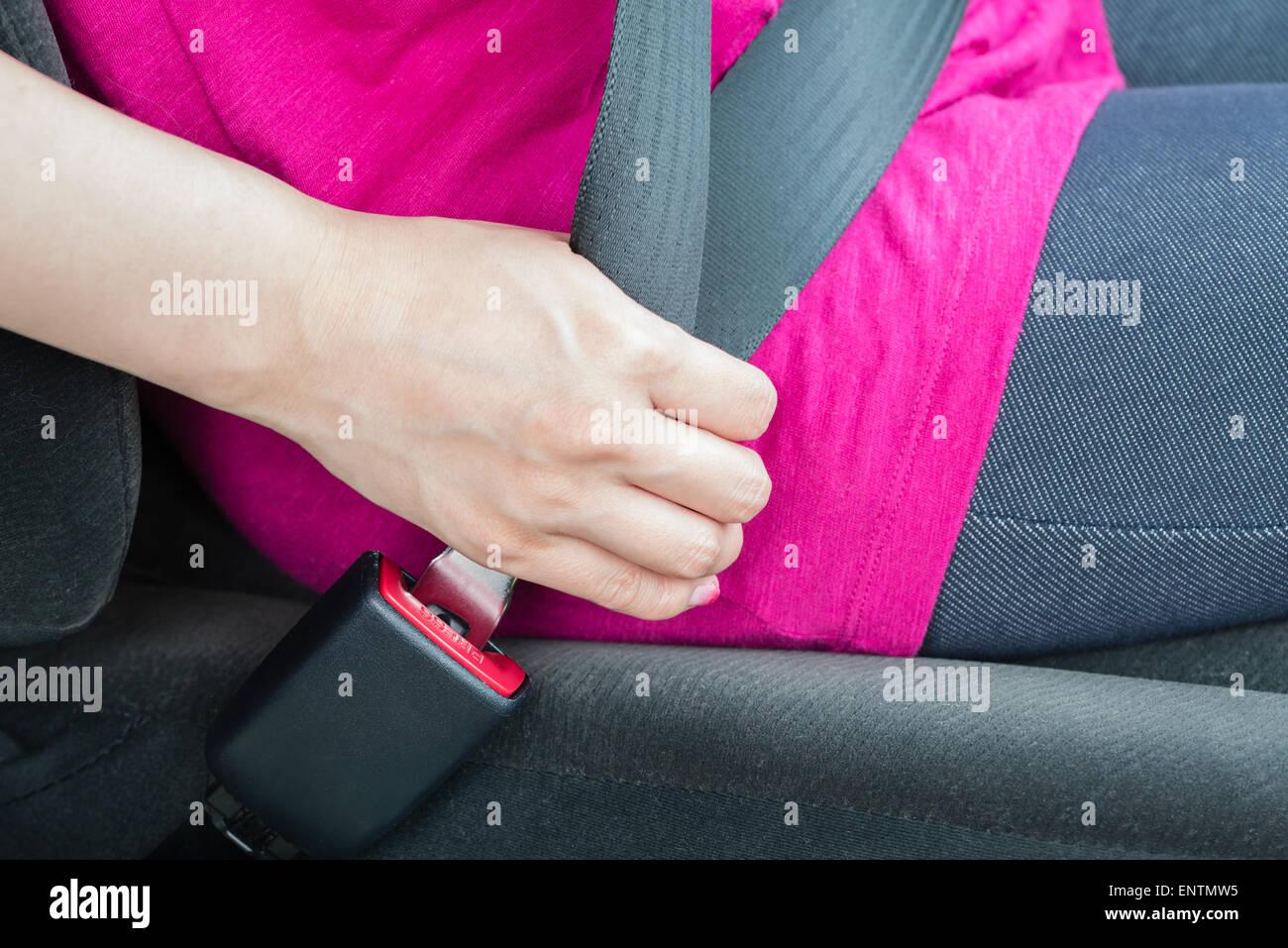 A girl wearing a pink shirt buckling a seatbelt Stock Photo