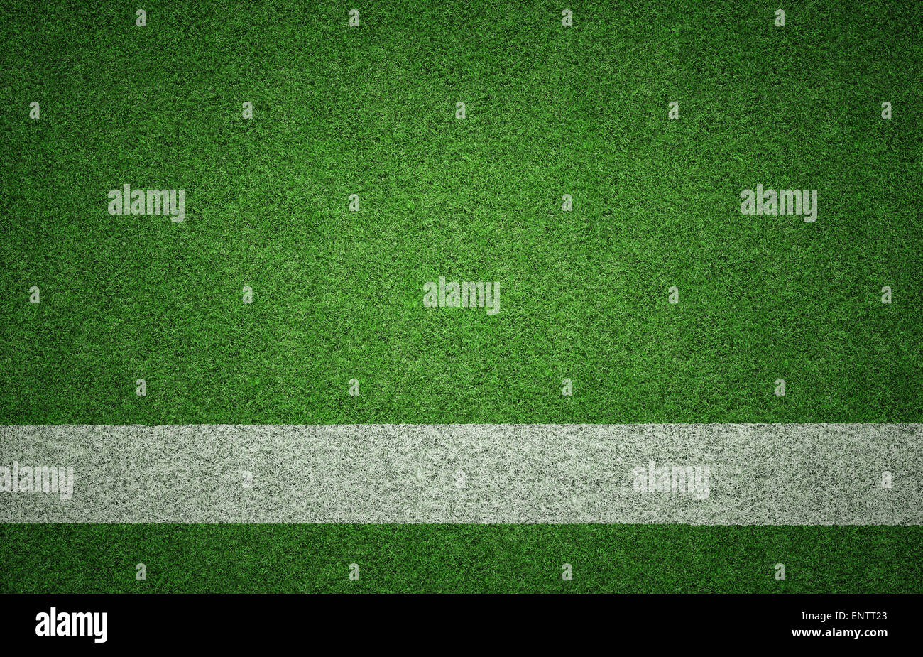 White painted line on green grass background texture with grunge lighting and lots of copy space. Perfect for sport - Stock Image