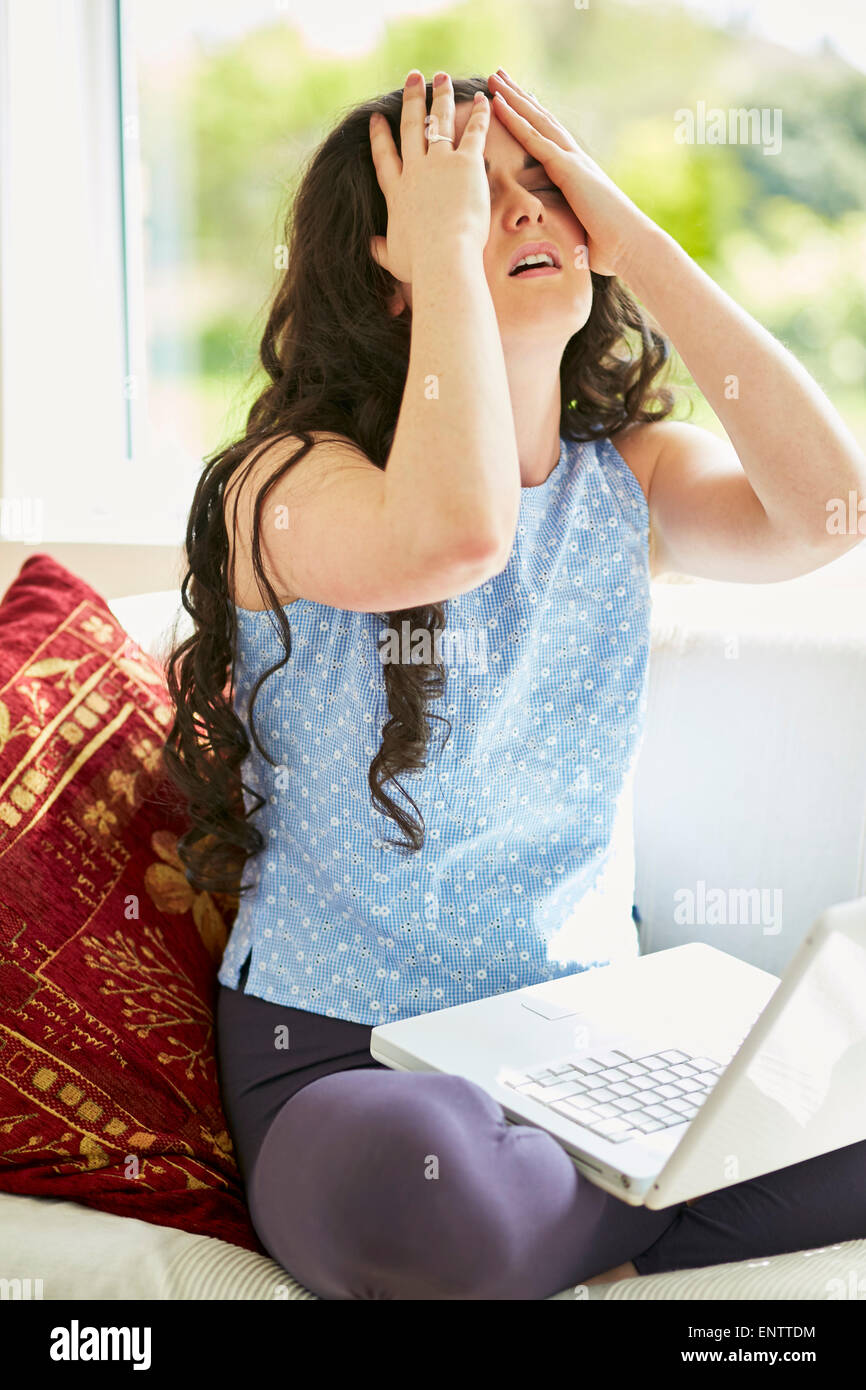 Stressed girl using laptop online - Stock Image