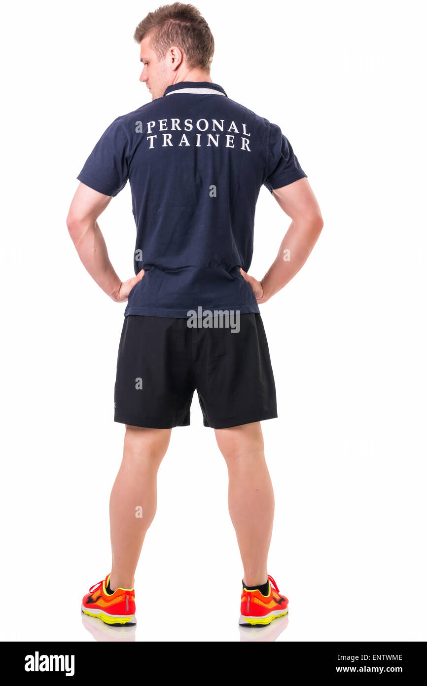 Handsome young personal trainer with clipboard, standing isolated on white background - Stock Image