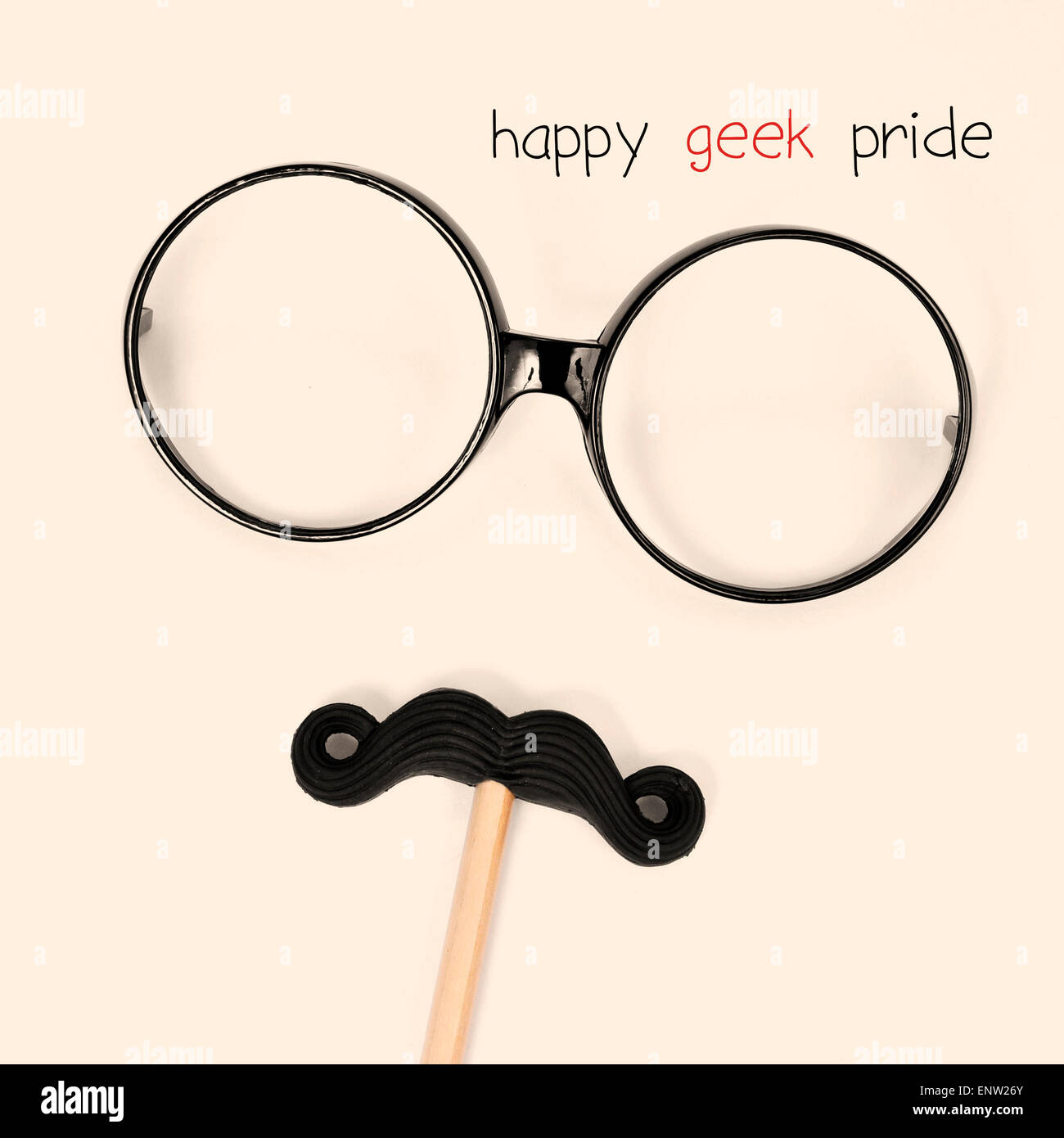 the text happy geek pride and a pair of round-framed eyeglasses and a moustache depicting a man face, on a beige - Stock Image