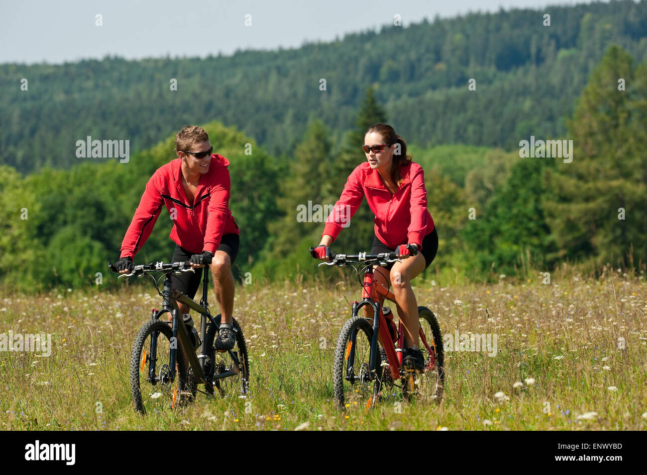 Young couple riding mountain bike in spring meadow - Stock Image