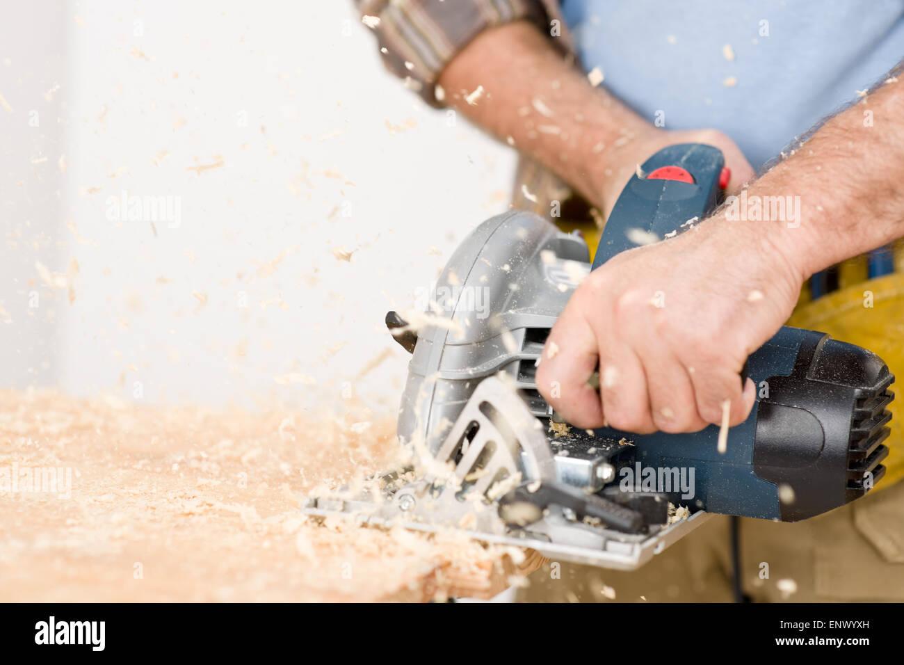 Home improvement - handyman cut wood with jigsaw Stock Photo