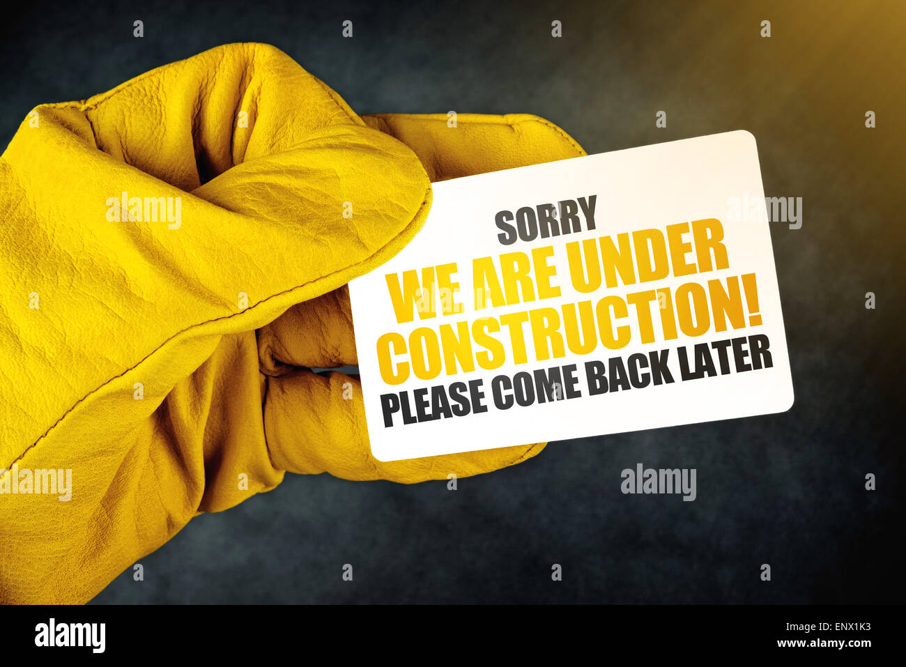 Under Construction on Business Card, Male Hand in Yellow Leather Construction Working Protective Gloves Holding Stock Photo