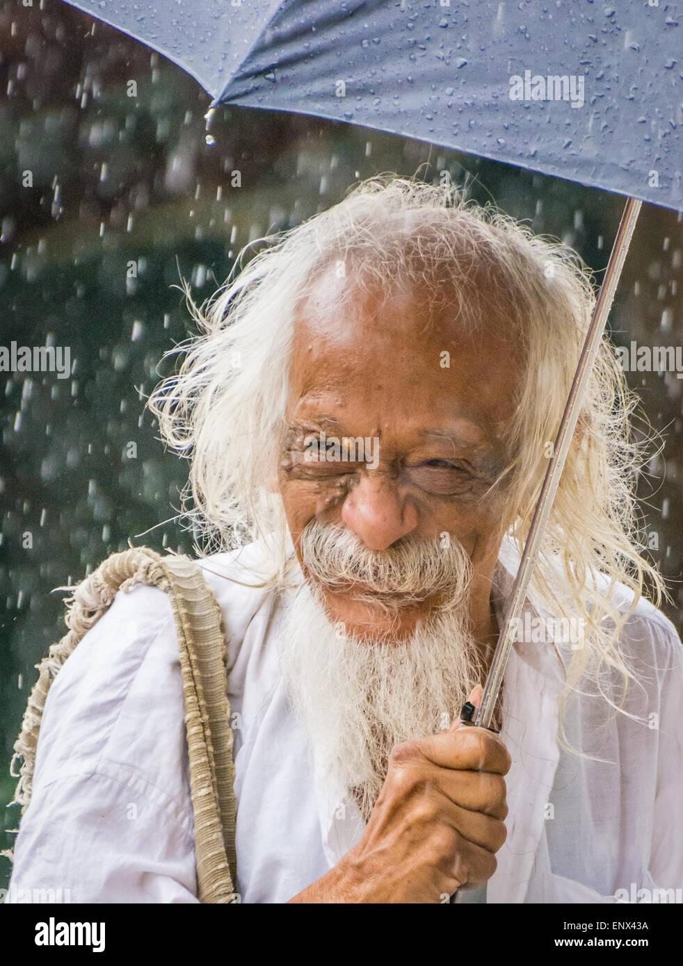 Sadhu holding an umbrella in the rain at the Sri Ramana Ashram in Tiruvannamalai, India - Stock Image