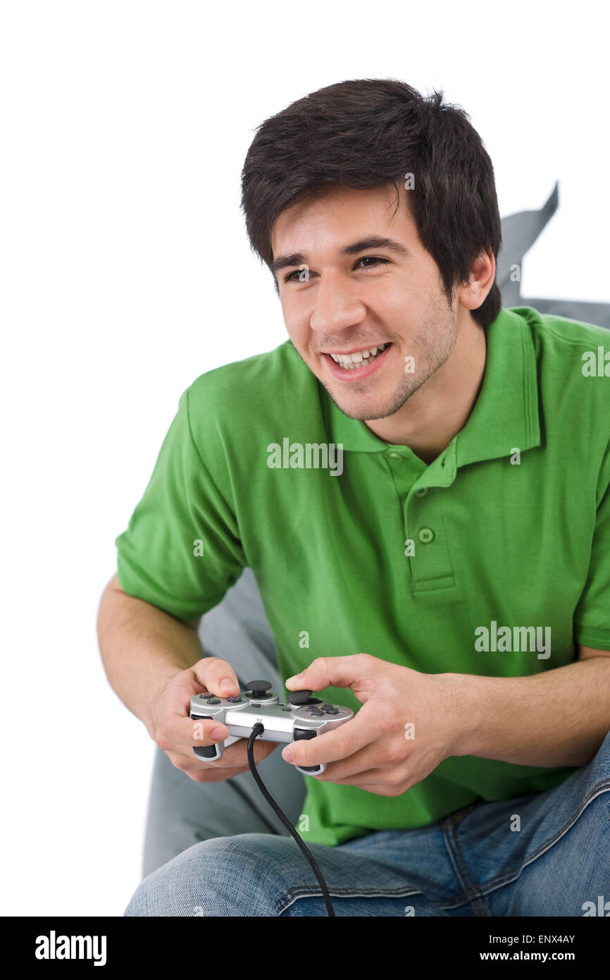 Young happy man playing video game with control pad - Stock Image