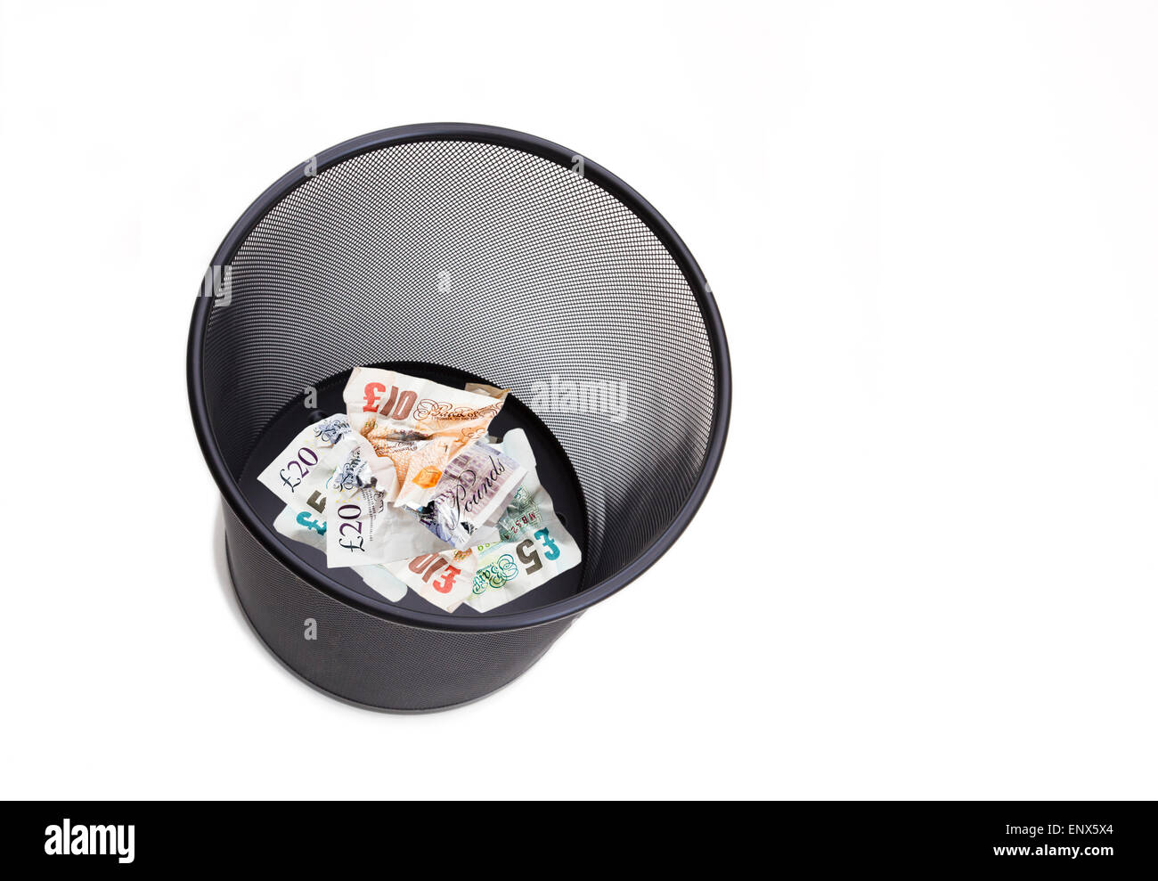 Sterling money pound notes pounds screwed up and thrown away in a wastepaper bin on white to illustrate wasting - Stock Image