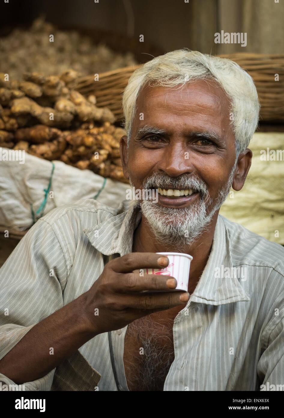 Portrait of a Indian vendor drinking tea in the vegetable market of Tiruvannamalai, India - Stock Image