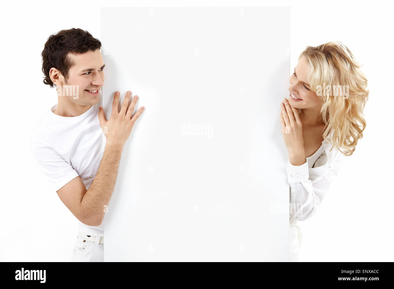 The guy and the girl exchange glances through an empty banner Stock Photo