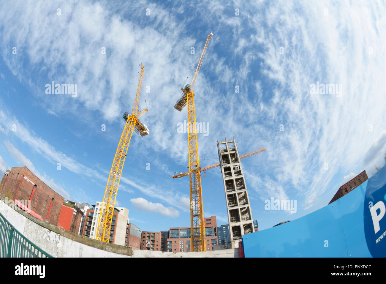 Yellow tower cranes against a blue sky with broken cloud formation - Stock Image