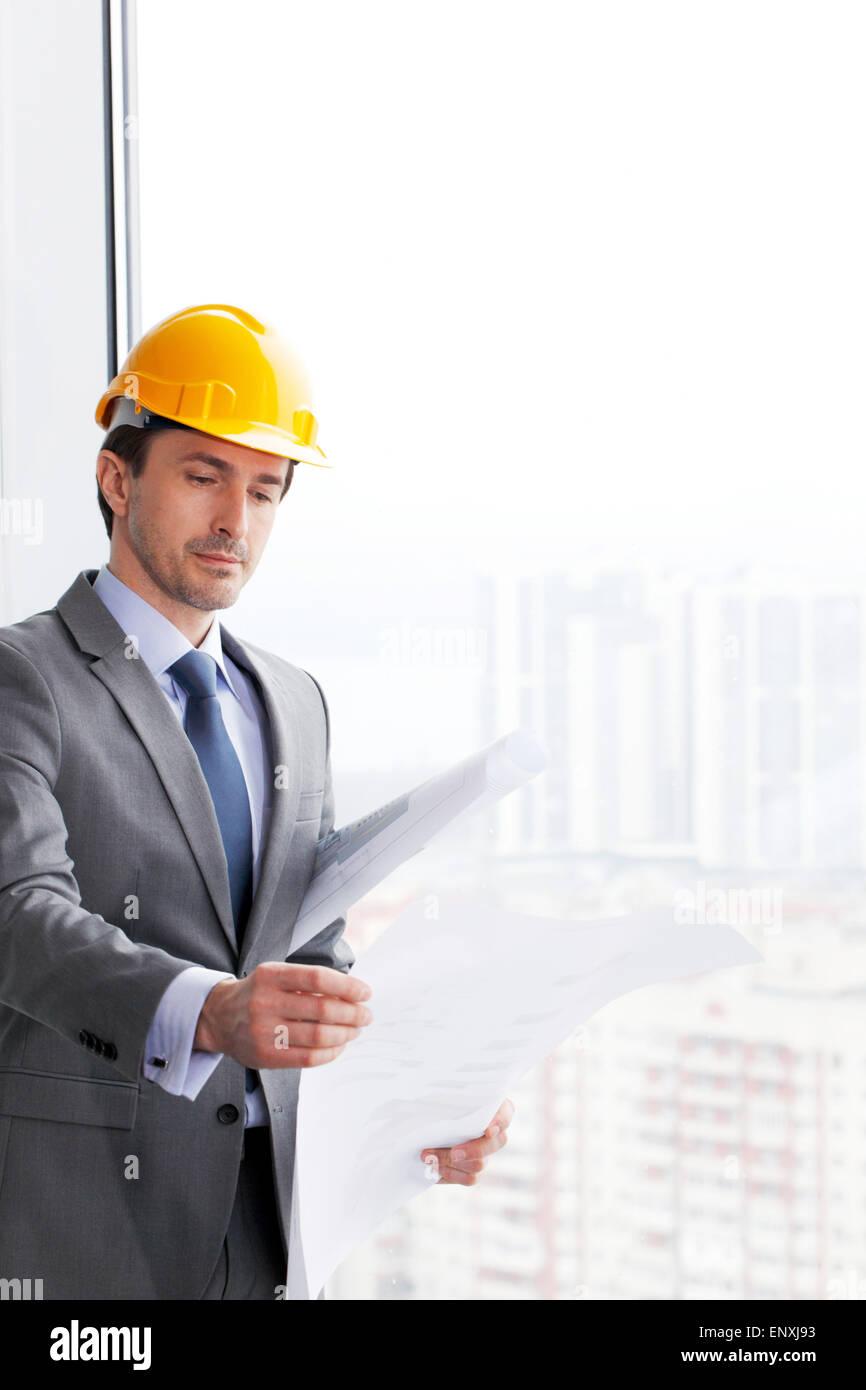 businessman in construction helmet looking at blueprint - Stock Image
