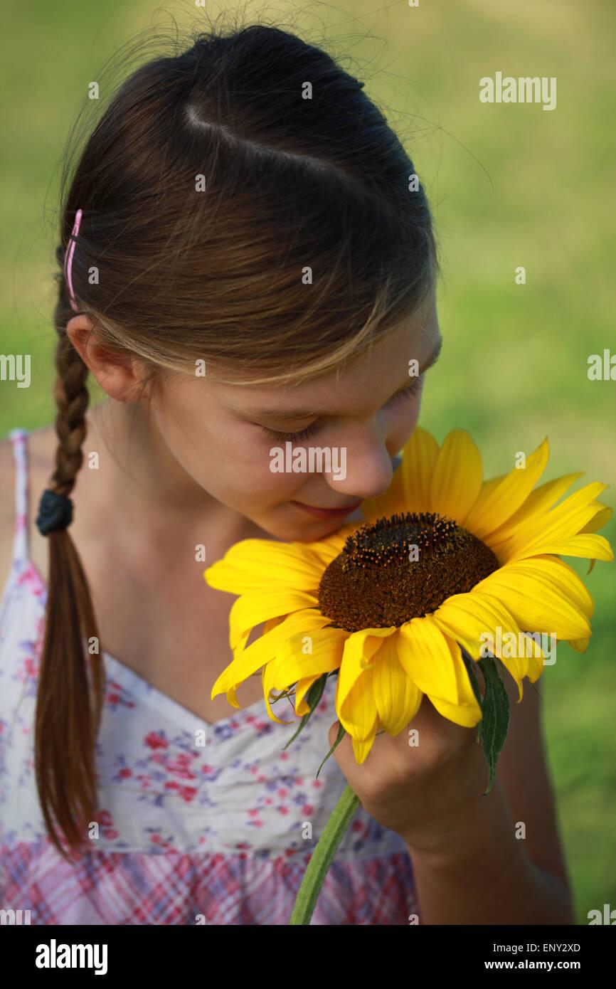 Mädchen riecht an einer Sonnenblume - Stock Image