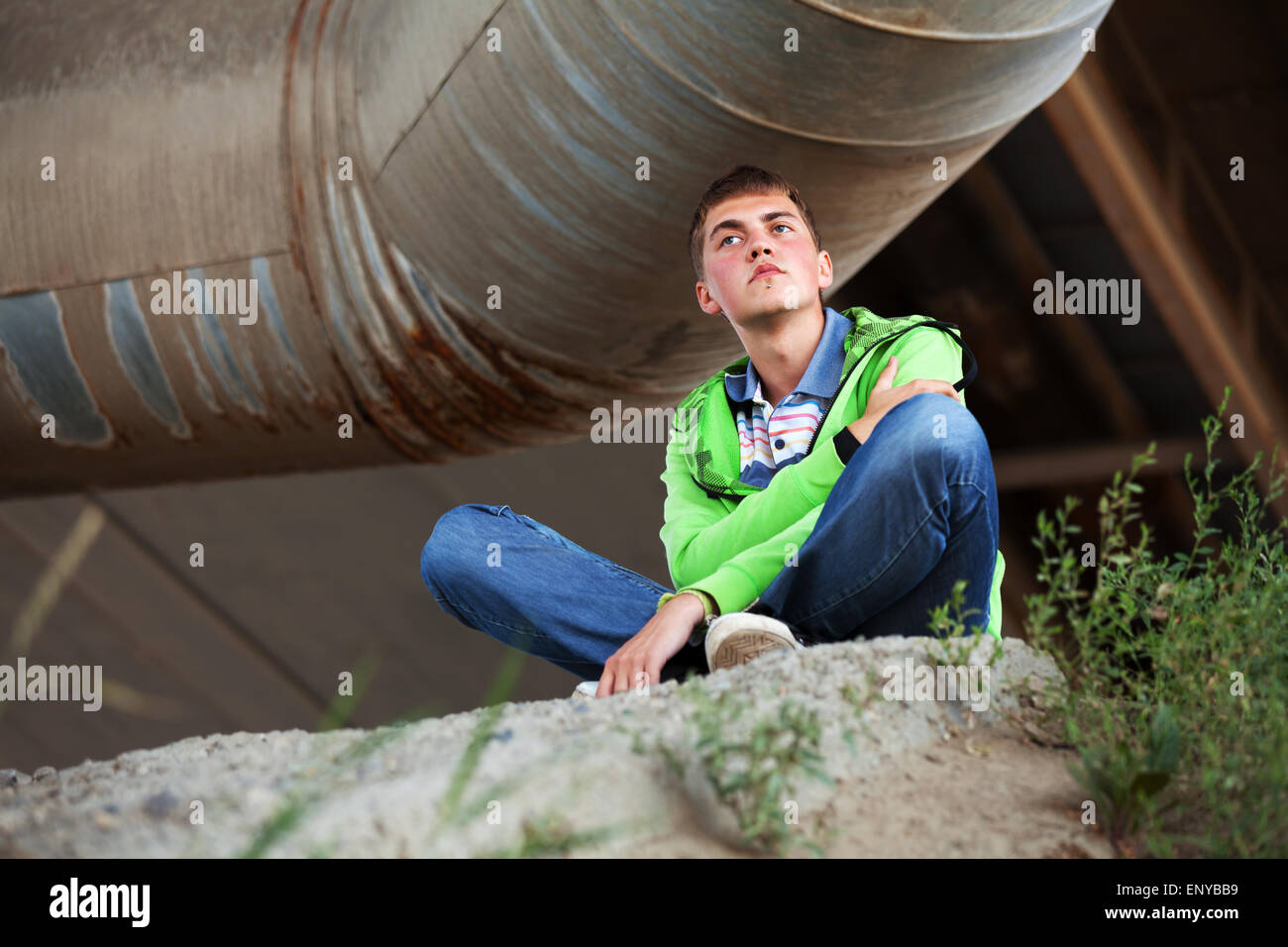 Young man sitting against industrial background - Stock Image