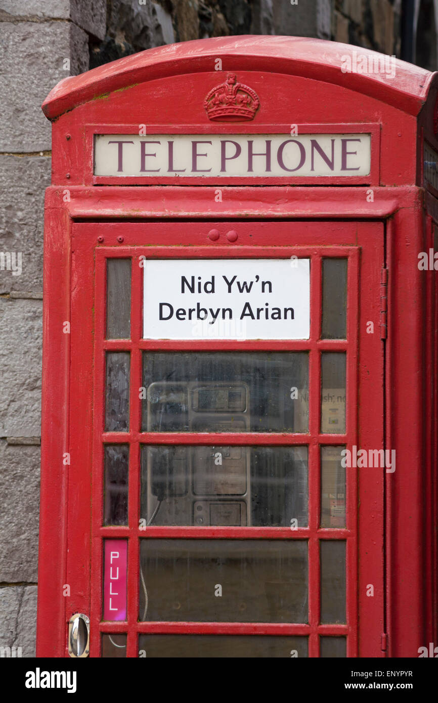 Red telephone box with sign in Welsh that it does not accept money, at Lower Fishguard or Abergwaun, Pembrokeshire, - Stock Image
