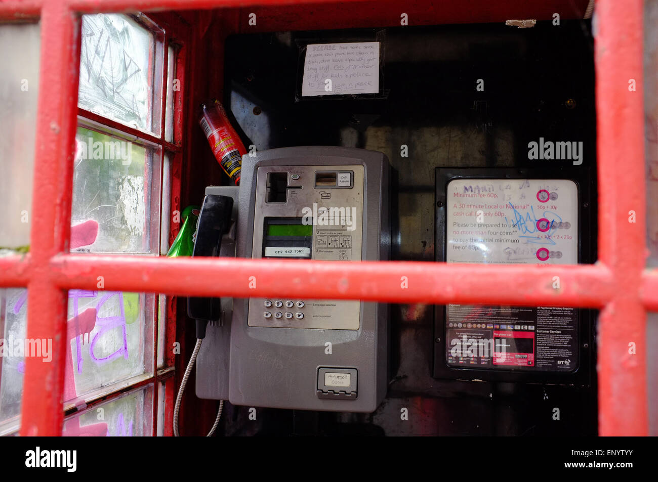 A vandalised red public telephone box in Bristol. - Stock Image