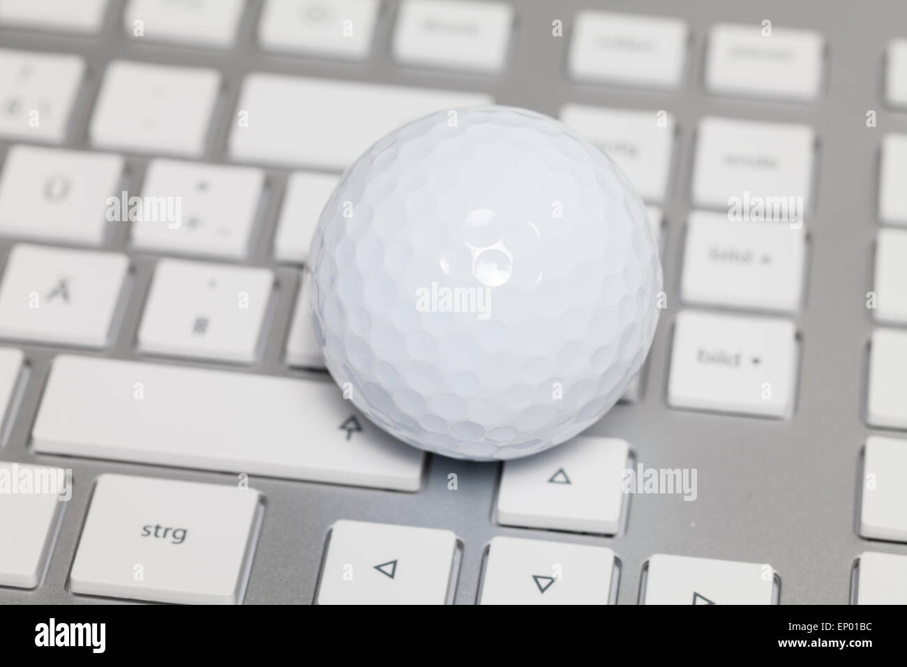 Golf ball on keyboard - Stock Image