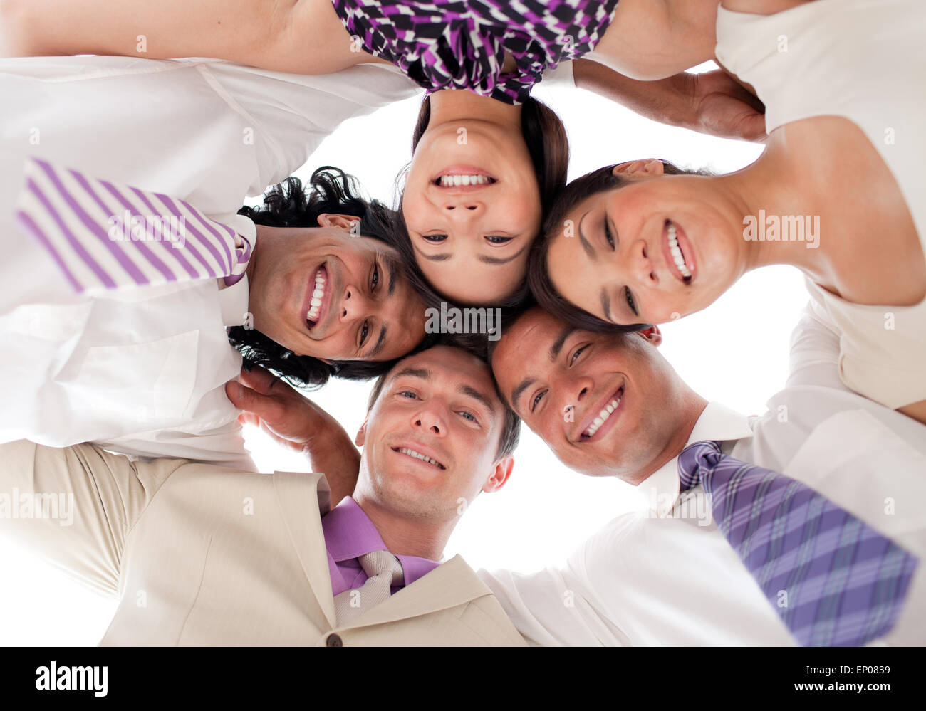 Smiling business team in a circle with heads together - Stock Image