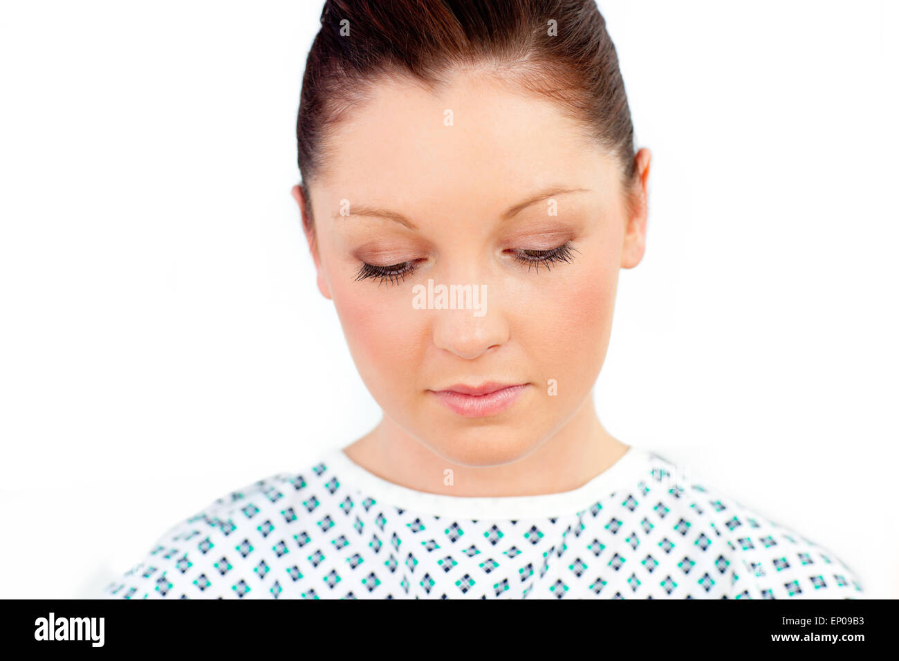 Close-up of a downcast patient against a white background - Stock Image