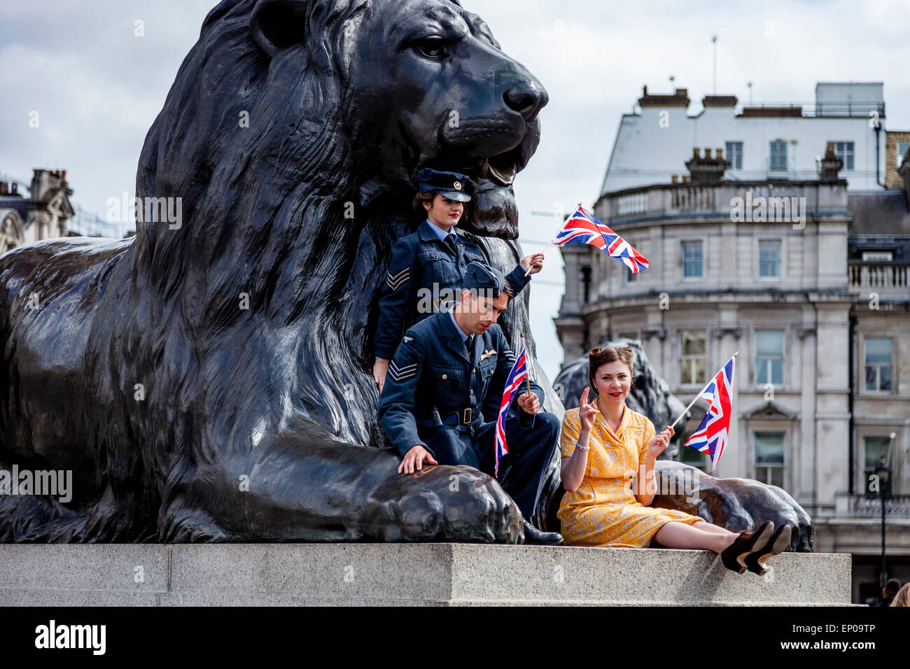 A Group Of People Dressed In 1940's Period Clothing Wave Union Flags In Trafalgar Square, London, England - Stock Image