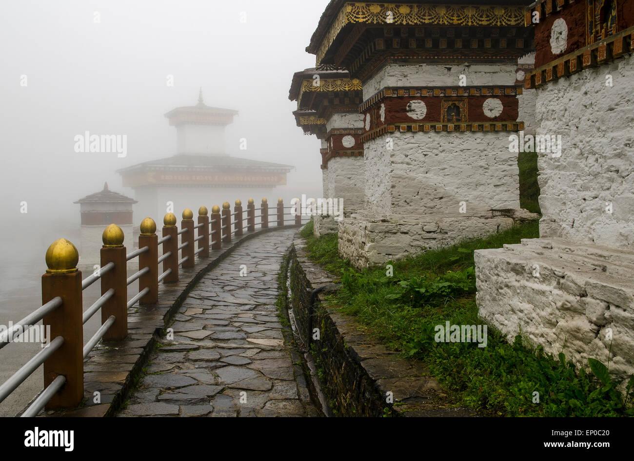 Chortens (Stupas) in fog, Dochu La Pass, Bhutan - Stock Image