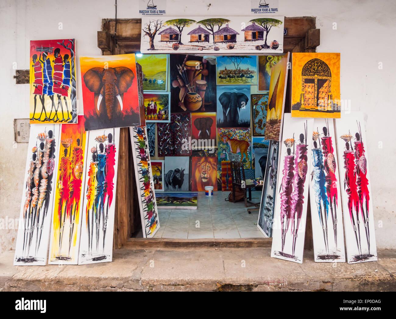 Store selling colorful tingatinga (tinga tinga) paintings as souvenirs for tourists in Stone Town, Zanzibar, Tanzania, - Stock Image